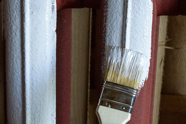 Brush in white paint stains the iron battery.