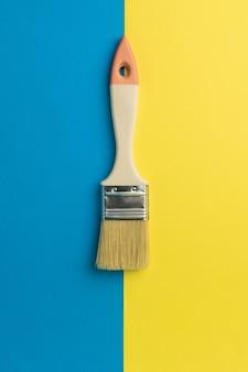 黄色と青の境界に木製のハンドルでブラシをかけます。クリエイティブキット。ミニマリズム。