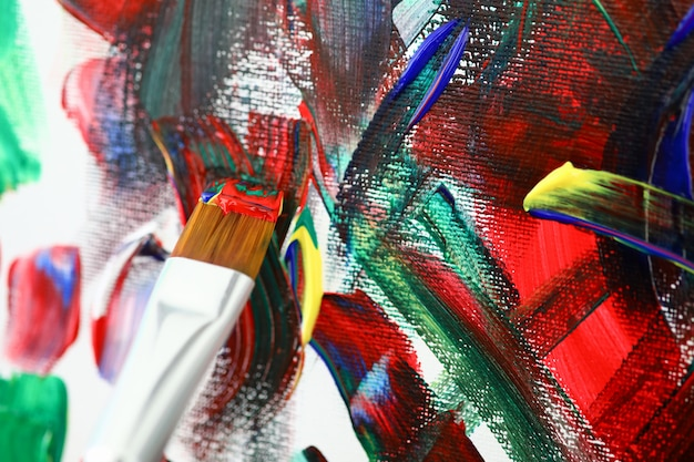 Brush with acrylic paint on background of art canvas