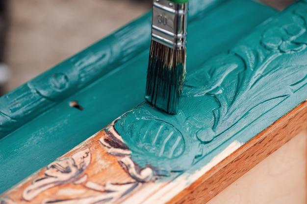 Кисть с синей или зеленой краской макро раскрашивает старую деревянную мебель для повторного использования экологичного образа жизни