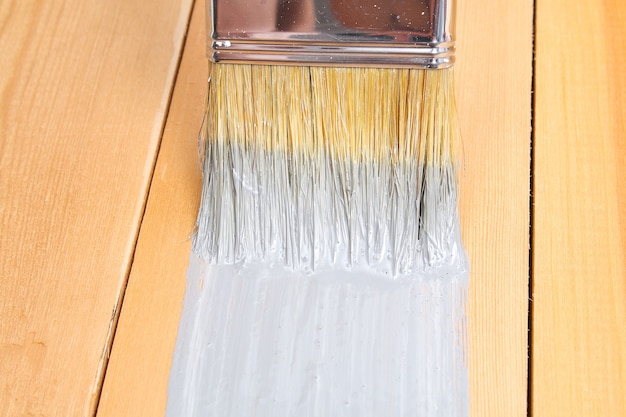 Brush with can paint in hand. a man paints wooden boards in a gray paint brush.