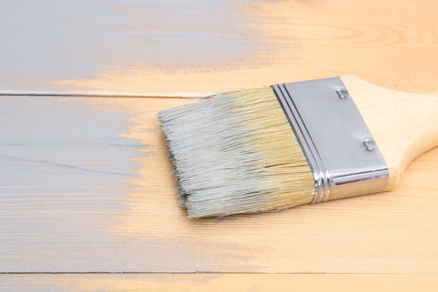 Brush with can paint in hand. man paints wooden boards in a gray paint brush.