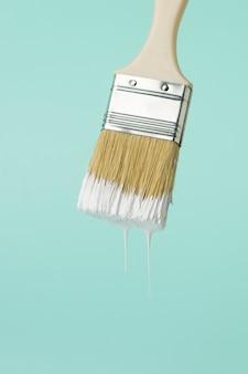 青い背景に白いペンキを滴下してブラシをかけます。塗装作業の実施。