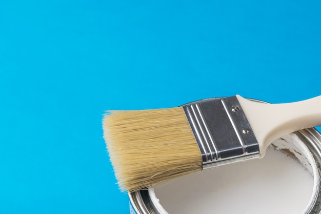 Brush with long bristles on an open can of paint on a blue surface