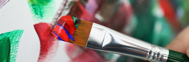 Brush with multicolored paints on background of picture