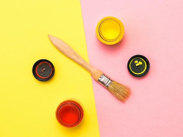 2色の表面に黄色と赤のペンキの開いた瓶でブラシをかけます