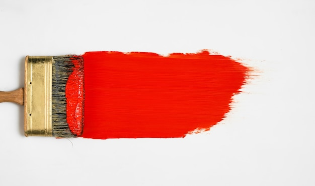 Brush with red paint lies on a white surface, top view, paint samples before work, choice of paints