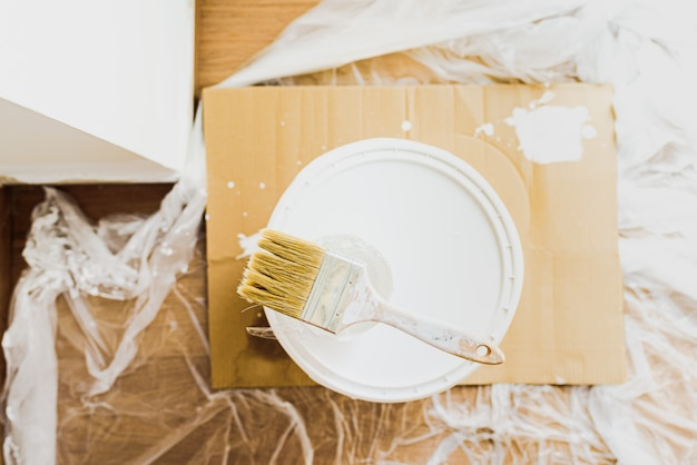Кисть с белой краской на ведре с пластиковой краской без запахов, экологическая. кисть с белой краской на ведре с пластиковой краской без запахов, экологическая.