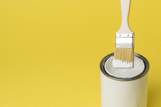 黄色の背景のペンキの缶の上に白いペンキでブラシをかけます。塗装作業の実施。テキストの場所。