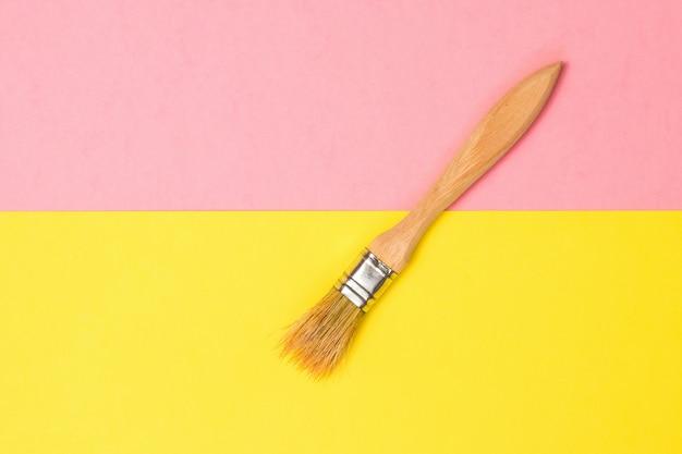 黄色とピンクの紙の表面に木製の柄が付いたブラシ