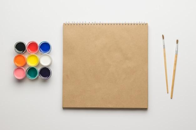 Кисти, набор красок и альбом для рисования на белом фоне.