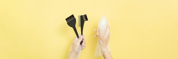 黄色の背景に手袋をした女性の手で家庭やサロンの染毛用のブラシとボウル