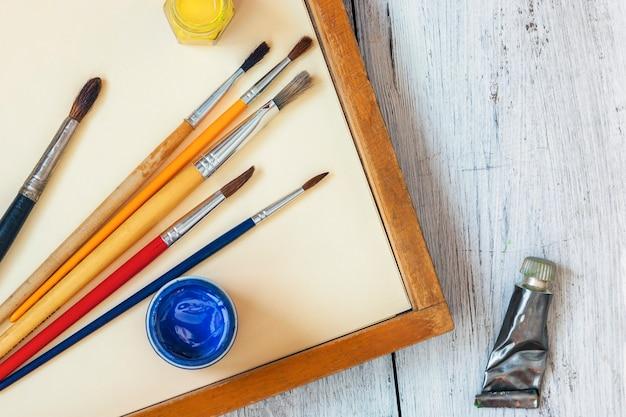 木製のテーブルに立つ缶のブラシと色のペンキ