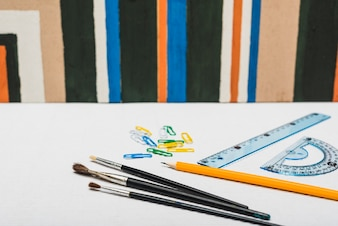 Brushes and stationery near abstract painting