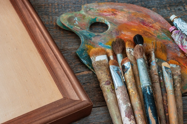 Brushes of the artist, tubes with oil paint, a frame with a canvas and a palette lie on the old easel in the workshop