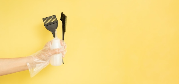 Brushes and bottle for hair dye on yellow background with copy space banner format