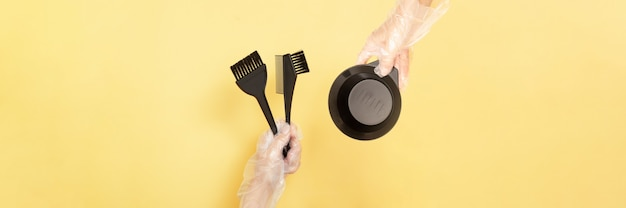 Brushes and bowl for home or salon hair dyeing in the hands of a woman with gloves on yellow background