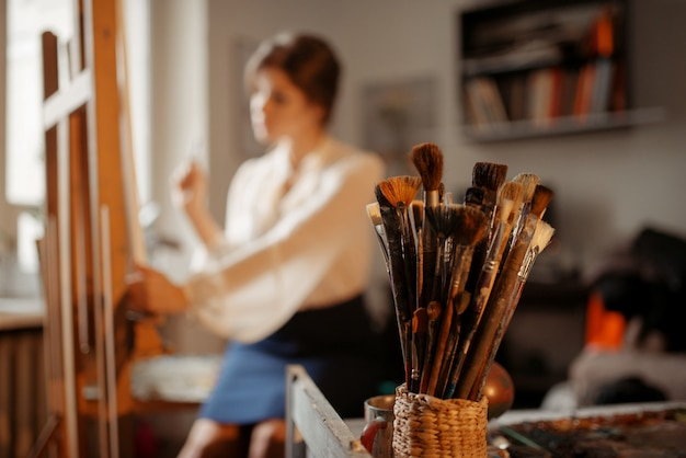 Коллекция кистей, художница работает за мольбертом в студии на заднем плане. творческая краска, художник рисует портрет в мастерской