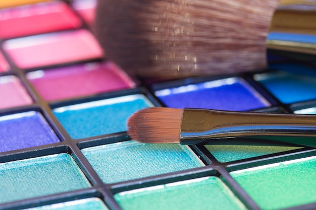Brushes on colorful eye shadows palette close up