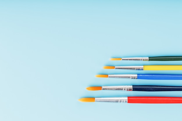 Brushes of different colors for drawing, creativity and art on a blue background.
