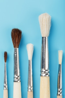 Brushes for drawing with paints made of natural wood and wool on a blue background.