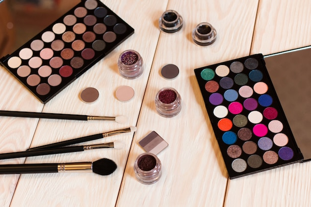 Brushes eyeshadow palettes and makeup tools collection on wooden desk