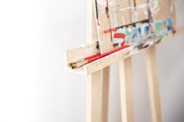 이젤, 흐릿한 배경, 복사 공간을 위해 나무 스탠드에 그림을 그리기 위한 브러시.