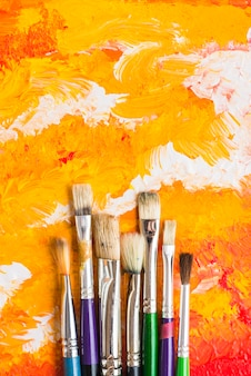 Brushes lying on orange painting