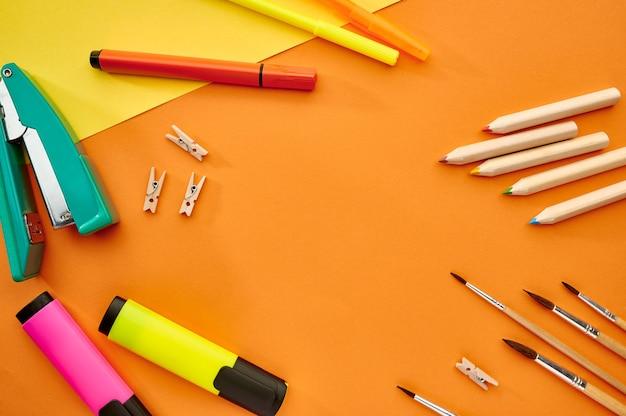 Кисти, маркеры и крупный план степлера на оранжевом фоне. канцелярские товары, школьные или образовательные принадлежности, инструменты для письма и рисования