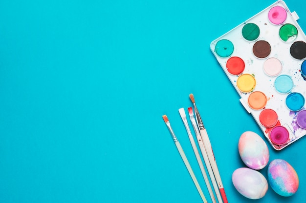 Brushes; painted easter eggs and plastic palette with water color on blue backdrop