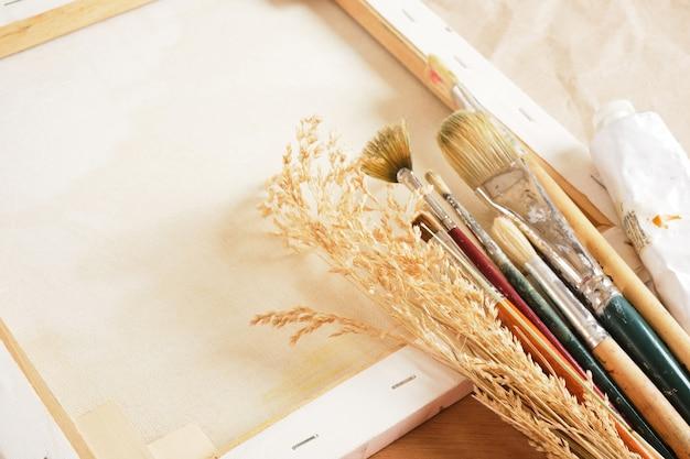 Кисти, краски в тубах, деревянная палитра, холст на подрамнике, бумага и белье на столе, мастерская художника.