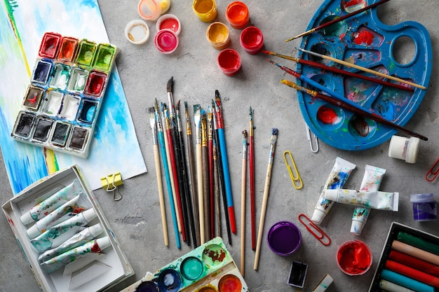 Brushes and paints of professional artist on table
