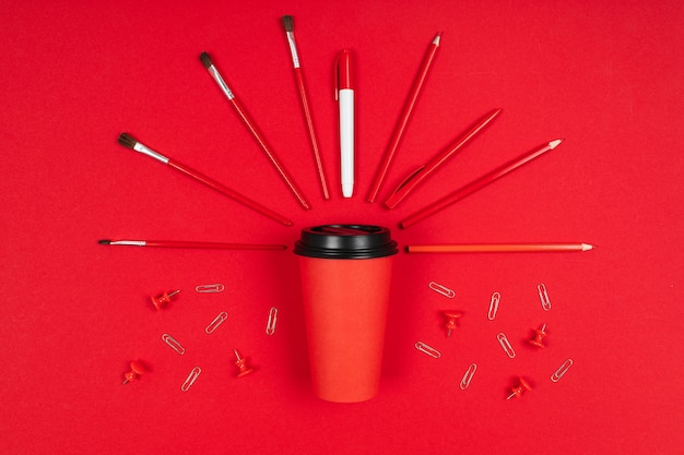 Brushes, paper clips, marker around a cup of coffee isolated on red background