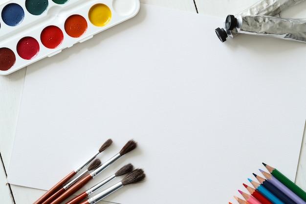 Кисти, карандаши и акварели, вид сверху фон