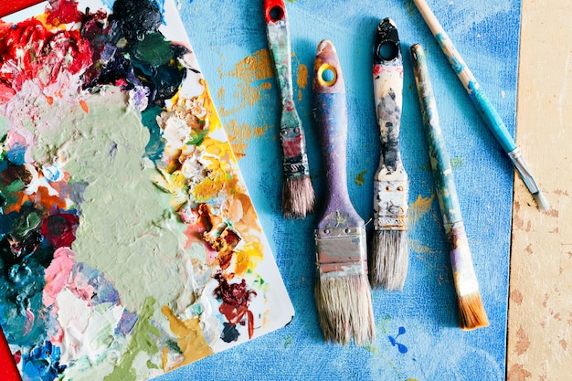 Brushes with palette in the creative composition. colorful element