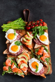 Brushetta or sandwich set on the board over black concrete.