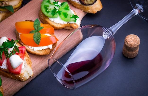 ワイン用のブルスケッタセット。黒の背景にさまざまな小さなサンドイッチ
