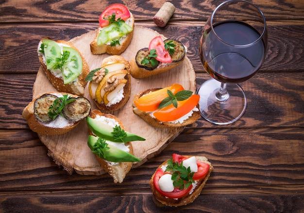 ワイン用のブルスケッタセット。木製の背景に小さなサンドイッチの様々な
