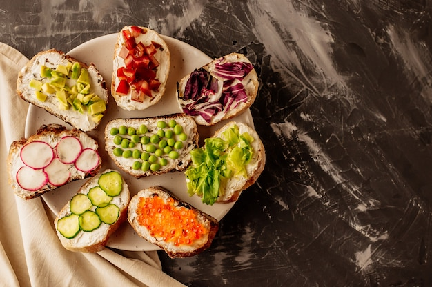 Brushettaまたは伝統的なスペインのタパス。木の板に設定された前菜イタリアの前菜スナック。