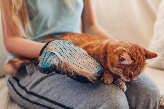Чистить кошку перчаткой для удаления шерсти домашних животных. забота о животных, расчесывающих его с помощью резиновой перчатки в домашних условиях