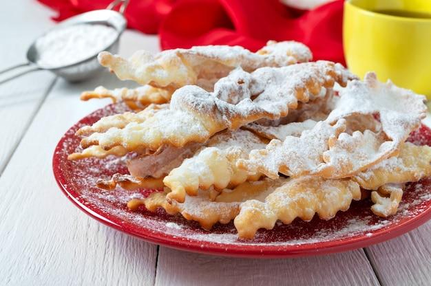 Brushwood  crispy deep fried cookies in powdered sugar with tea and jam