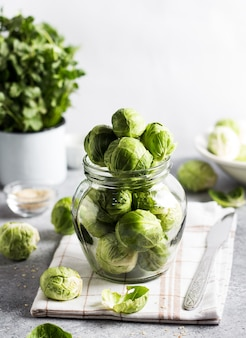Брюссельская капуста свежая органическая в банке на столе в кухне