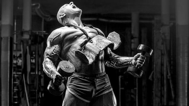 ジムでのトレーニングで筋肉をポンピングする残忍で筋肉質の強いボディービルダー運動選手