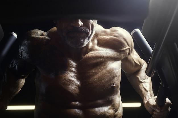 ジムでのトレーニングで筋肉をポンピングする残忍で筋肉質の強いボディービルダー運動男