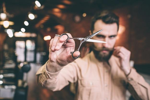 Брутальный и серьезный парикмахер держит ножницы в правой руке и смотрит сквозь него на камеру. также мужчина держит кусок своих усов.