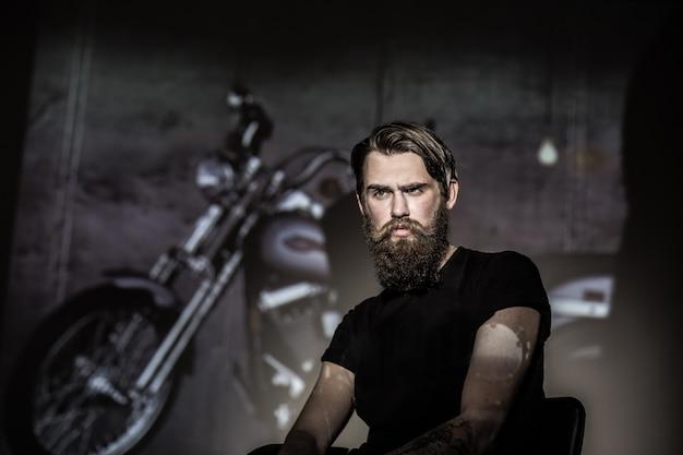 Brutal angry biker on a dark background.