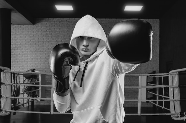 Brutal athlete boxing in the ring in a white hoodie covered with a hood. mixed martial arts concept.