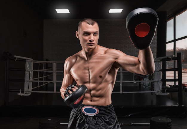 Brutal athlete holds boxing paws against the ring. mixed martial arts concept.
