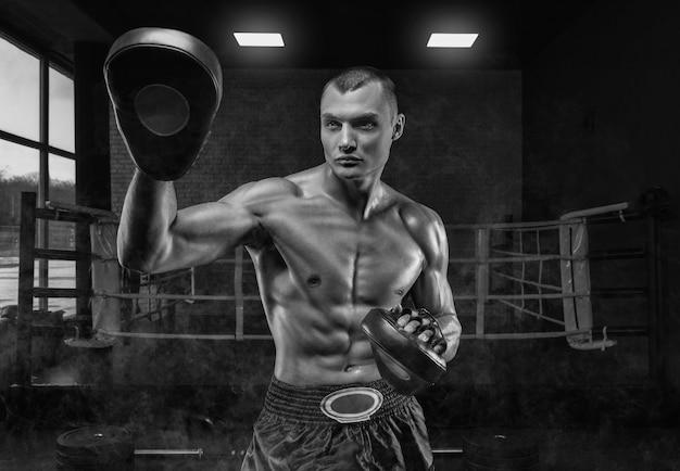 Жестокий спортсмен держит боксерские лапы против ринга. концепция смешанных боевых искусств.