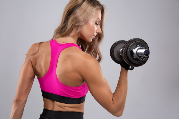 残忍なアスリートブロンドの女性はダンベルで彼女の筋肉をポンプでくみます